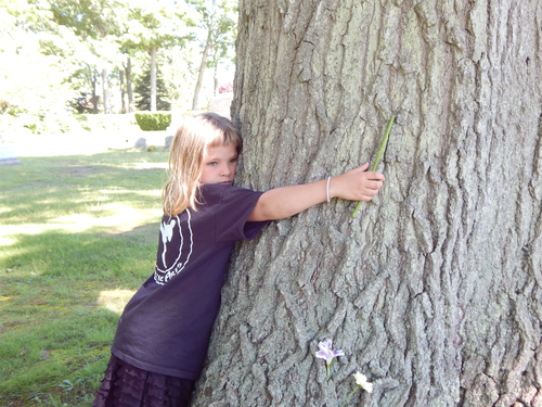 Joy hugs the tree planted in memory of Harry Faulk.